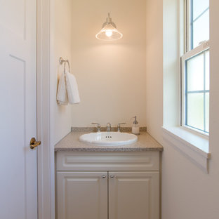Design ideas for a medium sized traditional cloakroom in Other with raised-panel cabinets, white cabinets, a one-piece toilet, white walls, a built-in sink, solid surface worktops, beige floors and beige worktops.