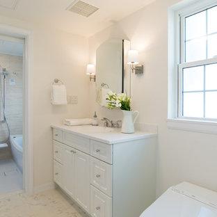 他の地域の広いトラディショナルスタイルのおしゃれなトイレ・洗面所 (レイズドパネル扉のキャビネット、白いキャビネット、一体型トイレ、ベージュのタイル、ライムストーンタイル、白い壁、一体型シンク、人工大理石カウンター、白い床、グレーの洗面カウンター) の写真