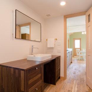 他の地域の中くらいのトロピカルスタイルのおしゃれなトイレ・洗面所 (シェーカースタイル扉のキャビネット、茶色いキャビネット、白い壁、無垢フローリング、ベッセル式洗面器、木製洗面台、茶色い床、ブラウンの洗面カウンター) の写真