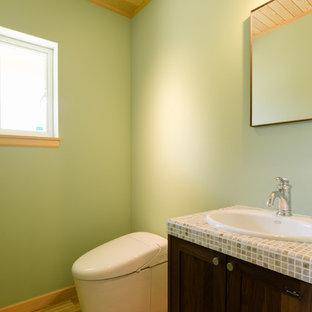 Foto di un bagno di servizio tropicale di medie dimensioni con ante in stile shaker, ante marroni, piastrelle multicolore, pareti verdi, pavimento in legno massello medio, top piastrellato, pavimento marrone, top multicolore e lavabo da incasso
