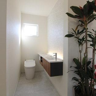 他の地域の小さいラスティックスタイルのおしゃれなトイレ・洗面所 (一体型トイレ、白い壁、クッションフロア、グレーの床) の写真