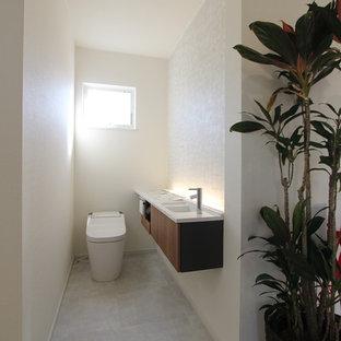 他の地域の中くらいのアジアンスタイルのおしゃれなトイレ・洗面所 (一体型トイレ、ベージュの壁、クッションフロア、横長型シンク、グレーの床、白い洗面カウンター) の写真