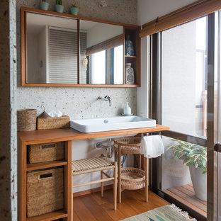 На фото: туалет в скандинавском стиле с коричневыми фасадами, разноцветными стенами, паркетным полом среднего тона, настольной раковиной, столешницей из дерева, коричневым полом и коричневой столешницей