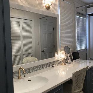 Immagine di un bagno di servizio chic con consolle stile comò, ante blu, piastrelle multicolore, piastrelle a mosaico, pareti bianche, pavimento in legno massello medio, lavabo integrato, top in superficie solida, pavimento marrone e top bianco