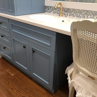 Ispirazione per un bagno di servizio tradizionale con consolle stile comò, ante blu, piastrelle multicolore, piastrelle a mosaico, pareti bianche, pavimento in legno massello medio, lavabo integrato, top in superficie solida, pavimento marrone e top bianco