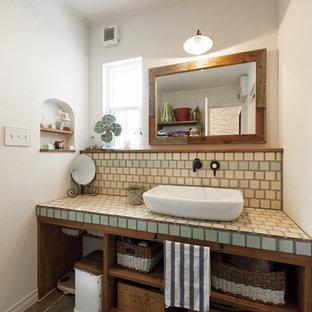 他の地域のカントリー風おしゃれなトイレ・洗面所 (オープンシェルフ、緑のタイル、ベージュのタイル、青いタイル、白い壁、ベッセル式洗面器、タイルの洗面台、黒い床) の写真