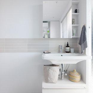 Ispirazione per un bagno di servizio minimalista con ante lisce, ante bianche, WC monopezzo, piastrelle a listelli, pareti bianche, pavimento con cementine, lavabo sospeso e pavimento grigio