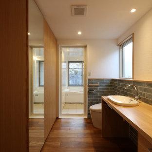 他の地域のミッドセンチュリースタイルのおしゃれなトイレ・洗面所 (一体型トイレ、磁器タイル、白い壁、濃色無垢フローリング、オーバーカウンターシンク、木製洗面台、茶色い床、ブラウンの洗面カウンター) の写真