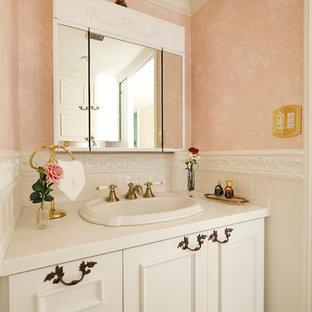 東京都下のトラディショナルスタイルのおしゃれなトイレ・洗面所 (落し込みパネル扉のキャビネット、白いキャビネット、ピンクの壁、オーバーカウンターシンク、茶色い床) の写真
