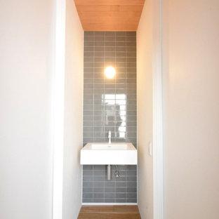他の地域のおしゃれなトイレ・洗面所 (グレーのタイル、磁器タイル、白い洗面カウンター、板張り天井) の写真