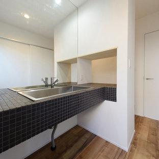 Стильный дизайн: туалет среднего размера в стиле модернизм с черной плиткой, плиткой мозаикой, белыми стенами, монолитной раковиной, столешницей из нержавеющей стали, коричневым полом, черной столешницей и встроенной тумбой - последний тренд