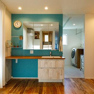 Inspiration pour un grand WC et toilettes urbain avec un mur bleu, un sol en bois clair, un sol marron, un placard sans porte, des portes de placard beiges, un lavabo encastré, un plan de toilette en bois, un plan de toilette marron, meuble-lavabo encastré, un plafond en papier peint et du papier peint.