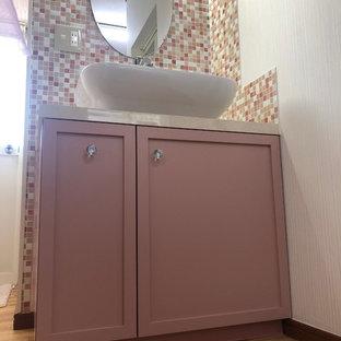 Inredning av ett eklektiskt litet rosa rosa toalett, med luckor med profilerade fronter, röda skåp, rosa kakel, mosaik, rosa väggar, linoleumgolv, ett nedsänkt handfat, träbänkskiva och beiget golv