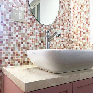 Réalisation d'un petit WC et toilettes bohème avec un placard à porte affleurante, des portes de placard rouges, un carrelage rose, carrelage en mosaïque, un mur rose, un sol en linoléum, un lavabo posé, un plan de toilette en bois, un sol beige, un plan de toilette rose, meuble-lavabo encastré, un plafond en papier peint et du papier peint.