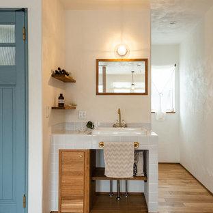Идея дизайна: туалет в стиле кантри с белой плиткой, белыми стенами, светлым паркетным полом, столешницей из плитки, бежевым полом, белой столешницей, плоскими фасадами, фасадами цвета дерева среднего тона и накладной раковиной
