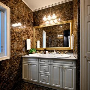 На фото: туалет в классическом стиле с фасадами с выступающей филенкой, белыми фасадами, коричневой плиткой, керамогранитной плиткой, коричневыми стенами, полом из керамогранита, накладной раковиной, столешницей из ламината, коричневым полом, серой столешницей и встроенной тумбой с