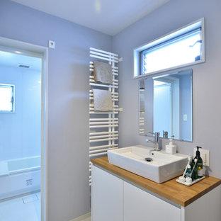 Пример оригинального дизайна интерьера: туалет в стиле модернизм с плоскими фасадами, белыми фасадами, фиолетовыми стенами, настольной раковиной, столешницей из дерева, белым полом и коричневой столешницей