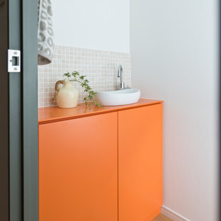 東京23区のコンテンポラリースタイルのおしゃれなトイレ・洗面所 (フラットパネル扉のキャビネット、オレンジのキャビネット、ベージュのタイル、モザイクタイル、白い壁、無垢フローリング、ベッセル式洗面器、茶色い床、ベージュのカウンター、造り付け洗面台) の写真