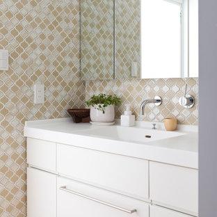 東京23区のコンテンポラリースタイルのおしゃれなトイレ・洗面所 (フラットパネル扉のキャビネット、白いキャビネット、ベージュのタイル、淡色無垢フローリング、一体型シンク、茶色い床、白い洗面カウンター、造り付け洗面台) の写真