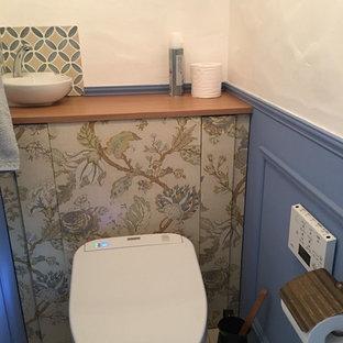 Ejemplo de aseo romántico, pequeño, con armarios tipo vitrina, sanitario de una pieza, baldosas y/o azulejos naranja, paredes azules, suelo de madera oscura, lavabo bajoencimera, suelo marrón y encimeras beige
