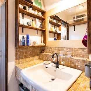 Cette image montre un petit WC et toilettes nordique avec un WC à poser, un carrelage beige, un carrelage de pierre, un mur blanc, un sol en bois clair, un lavabo encastré, un plan de toilette en travertin, un sol marron et un plan de toilette beige.