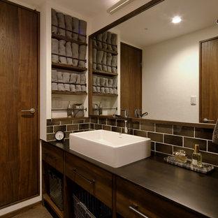 他の地域のミッドセンチュリースタイルのおしゃれなトイレ・洗面所 (フラットパネル扉のキャビネット、ヴィンテージ仕上げキャビネット、白い壁、ベッセル式洗面器、茶色い床) の写真