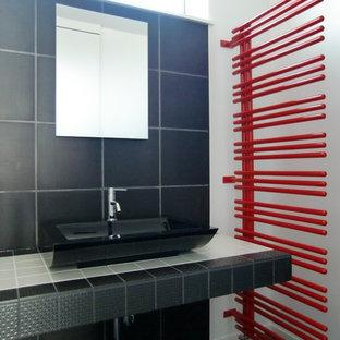 На фото: туалеты в стиле модернизм с настольной раковиной, столешницей из плитки, черным полом, черной плиткой, керамогранитной плиткой, белыми стенами, полом из фанеры и черной столешницей