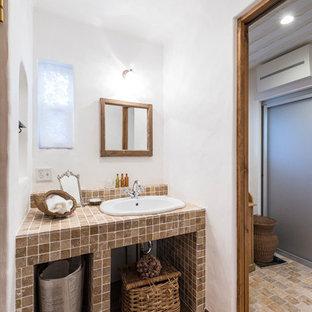 На фото: маленький туалет в средиземноморском стиле с коричневой плиткой, каменной плиткой, белыми стенами, светлым паркетным полом, столешницей из плитки, коричневым полом, бежевой столешницей и накладной раковиной с