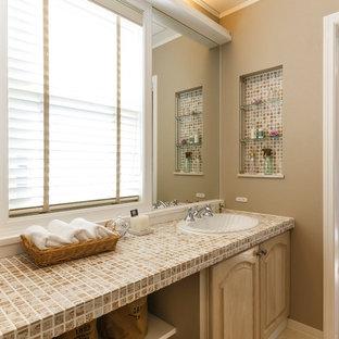 Неиссякаемый источник вдохновения для домашнего уюта: туалет в современном стиле с фасадами с утопленной филенкой, светлыми деревянными фасадами, коричневыми стенами, накладной раковиной, столешницей из плитки, бежевым полом и бежевой столешницей