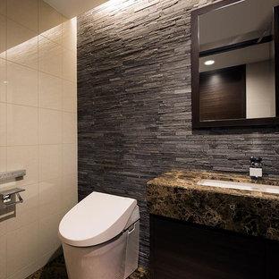 モダンスタイルのおしゃれなトイレ・洗面所 (茶色いキャビネット、一体型トイレ、モノトーンのタイル、マルチカラーの壁、大理石の床、アンダーカウンター洗面器、大理石の洗面台、茶色い床、ブラウンの洗面カウンター) の写真