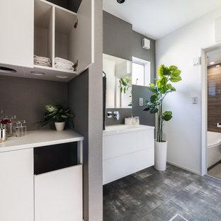 ラスティックスタイルのおしゃれなトイレ・洗面所 (フラットパネル扉のキャビネット、白いキャビネット、グレーの壁、グレーの床) の写真