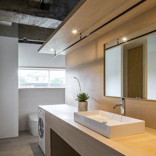 東京都下の中くらいのインダストリアルスタイルのおしゃれなトイレ・洗面所 (オープンシェルフ、ベージュのキャビネット、白い壁、磁器タイルの床、木製洗面台、グレーの床、ベージュのカウンター、造り付け洗面台、壁紙) の写真