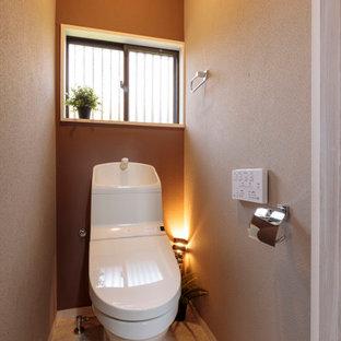 Imagen de aseo romántico con sanitario de una pieza, paredes grises, suelo de contrachapado, lavabo integrado y suelo beige