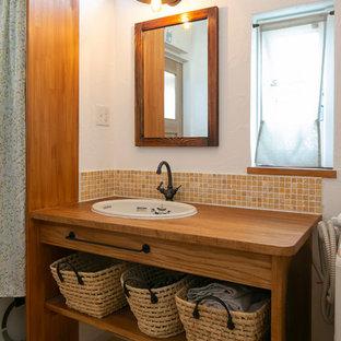 他の地域のカントリー風おしゃれなトイレ・洗面所 (オレンジのタイル、石タイル、白い壁、木製洗面台、ブラウンの洗面カウンター、無垢フローリング、オーバーカウンターシンク、茶色い床) の写真