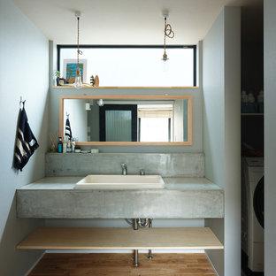 他の地域のビーチスタイルのおしゃれなトイレ・洗面所 (コンクリートの洗面台、グレーの洗面カウンター) の写真