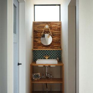 他の地域のビーチスタイルのおしゃれなトイレ・洗面所 (青いタイル、モザイクタイル、木製洗面台、白い洗面カウンター) の写真