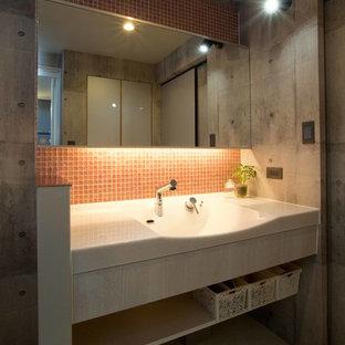 他の地域の中くらいのインダストリアルスタイルのおしゃれなトイレ・洗面所 (濃色木目調キャビネット、ピンクのタイル、ガラスタイル、グレーの壁、クッションフロア、一体型シンク、人工大理石カウンター、ベージュの床、白い洗面カウンター) の写真