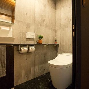 他の地域の中くらいのインダストリアルスタイルのおしゃれなトイレ・洗面所 (濃色木目調キャビネット、一体型トイレ、グレーの壁、クッションフロア、黒い床、フラットパネル扉のキャビネット、ベッセル式洗面器) の写真