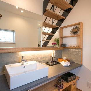 Foto de aseo asiático con armarios abiertos, paredes blancas, suelo de madera en tonos medios, lavabo con pedestal y suelo marrón