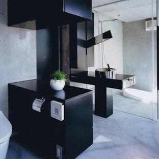他の地域のコンテンポラリースタイルのおしゃれなトイレ・洗面所 (黒いキャビネット、グレーの壁、ベッセル式洗面器、グレーの床、黒い洗面カウンター) の写真