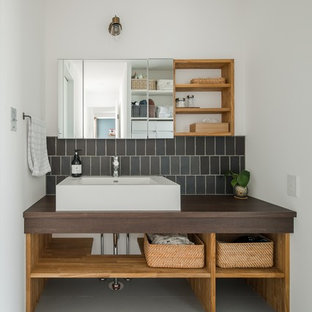 他の地域の広いアジアンスタイルのおしゃれなトイレ・洗面所 (オープンシェルフ、ベージュのキャビネット、分離型トイレ、黒いタイル、磁器タイル、白い壁、クッションフロア、オーバーカウンターシンク、木製洗面台、グレーの床、ブラウンの洗面カウンター) の写真