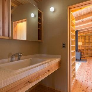 Esempio di un grande bagno di servizio stile rurale con nessun'anta, bidè, pareti beige, pavimento in legno massello medio, lavabo da incasso, top piastrellato e pavimento beige
