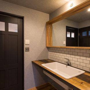 Inspiration pour un WC et toilettes urbain de taille moyenne avec un placard sans porte, des portes de placard grises, un bidet, un carrelage blanc, des carreaux de céramique, un mur gris, un sol en bois clair, un lavabo posé, un plan de toilette en bois, un sol beige, un plan de toilette marron, meuble-lavabo encastré, un plafond en papier peint et du papier peint.