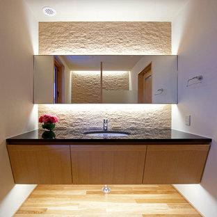 Réalisation de WC et toilettes design avec un placard à porte plane, des portes de placard en bois clair, un carrelage beige, un mur beige, un sol en bois clair, un lavabo encastré et un sol beige.