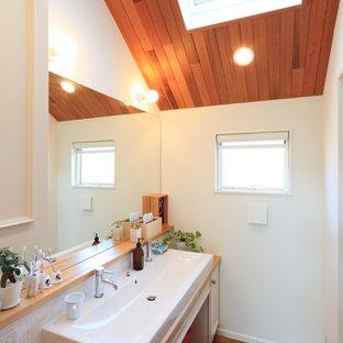 Réalisation d'un WC et toilettes asiatique avec des portes de placard blanches, carrelage en mosaïque, un mur blanc, un sol en bois brun, une grande vasque, un plan de toilette en bois, un sol marron et un plan de toilette marron.