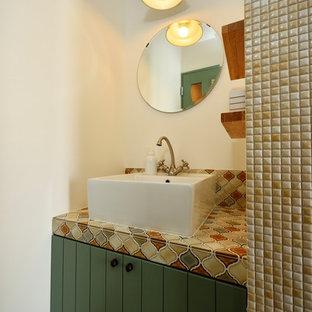 他の地域の地中海スタイルのおしゃれなトイレ・洗面所 (家具調キャビネット、緑のキャビネット、白い壁、ベッセル式洗面器、グレーの床) の写真