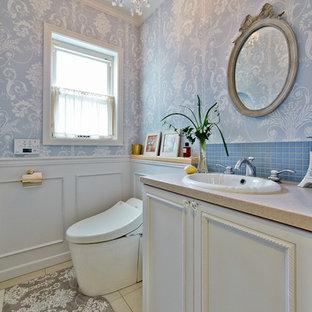 Свежая идея для дизайна: туалет в классическом стиле с фасадами с утопленной филенкой, белыми фасадами, синей плиткой, синими стенами, мраморным полом, накладной раковиной и бежевым полом - отличное фото интерьера