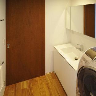 Неиссякаемый источник вдохновения для домашнего уюта: маленький туалет в современном стиле с плоскими фасадами, белыми фасадами, плиткой из сланца, белыми стенами, полом из фанеры, монолитной раковиной, столешницей из искусственного камня, коричневым полом и белой столешницей