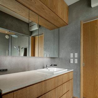 На фото: туалеты среднего размера в стиле модернизм с плоскими фасадами, фасадами цвета дерева среднего тона, серыми стенами, полом из керамической плитки, накладной раковиной, столешницей из искусственного кварца, серым полом и разноцветной столешницей