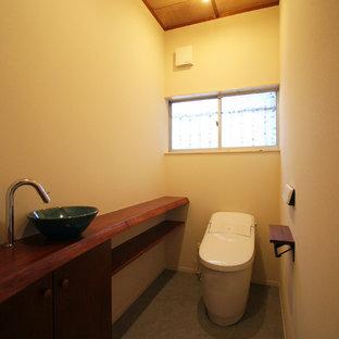 Ispirazione per un bagno di servizio etnico con pareti beige, pavimento in cemento, lavabo a bacinella e pavimento grigio